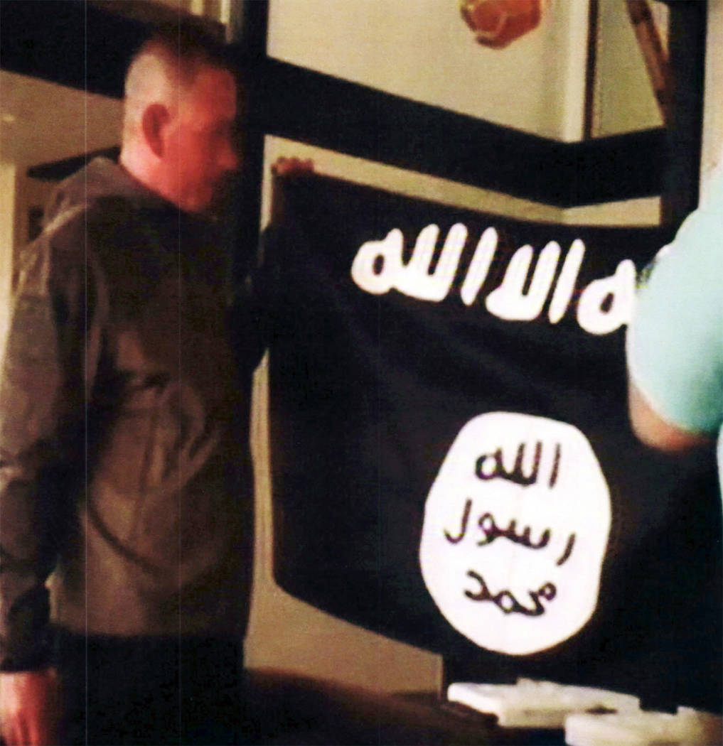 FILE - In this July 8, 2017 file image taken from FBI video and provided by the U.S. Attorney's Office in Hawaii on July 13, 2017, Army Sgt. 1st Class Ikaika Kang holds an Islamic State group flag ...