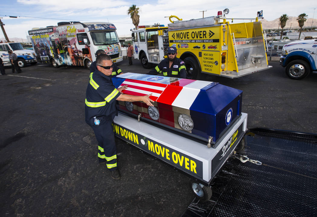 Andres Werne of Big Valley Towing, left, helps move the ceremonial casket after the Spirit Ride ceremony at Big Valley Towing in North Las Vegas on Thursday, Aug. 30, 2018. The cross-country event ...