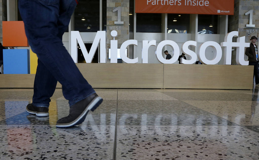 A man walks past a Microsoft sign set up for the Microsoft BUILD conference at Moscone Center in San Francisco on April 28, 2015. Microsoft says it's requiring its U.S. suppliers to offer their ...