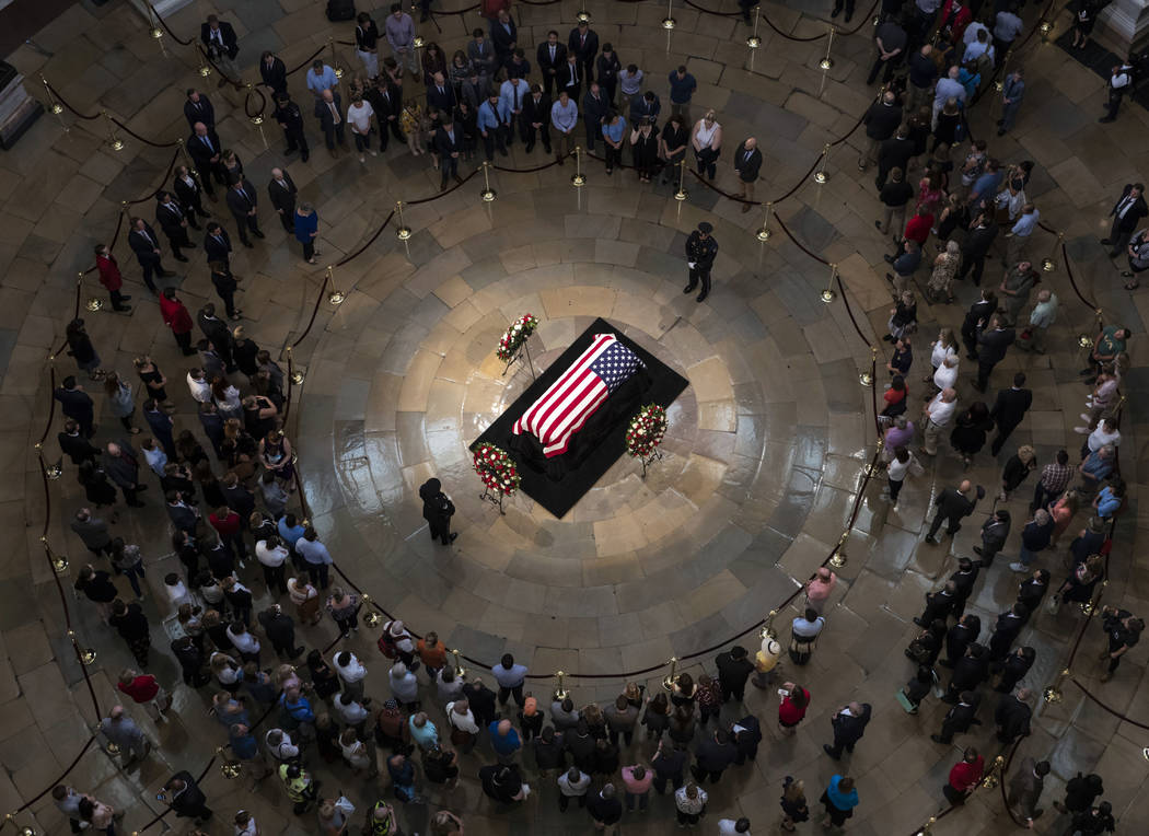Members of the public walk past the flag-draped casket bearing the remains of John McCain of Arizona, who lived and worked in Congress over four decades, in the U.S. Capitol rotunda in Washington, ...
