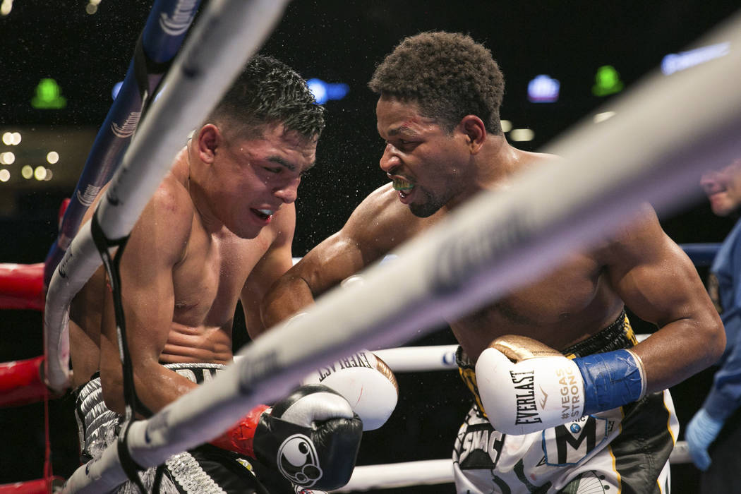 Shawn Porter, right, pushes Adrian Granados against the ropes during the WBC silver welterweight boxing bout Saturday, Nov. 4, 2017, in New York. Porter won the fight. (AP Photo/Kevin Hagen)