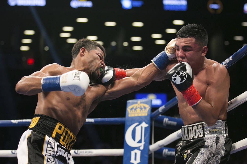 Shawn Porter, left, and Adrian Granados connect with punches during the WBC silver welterweight boxing bout Saturday, Nov. 4, 2017, in New York. Porter won the fight. (AP Photo/Kevin Hagen)
