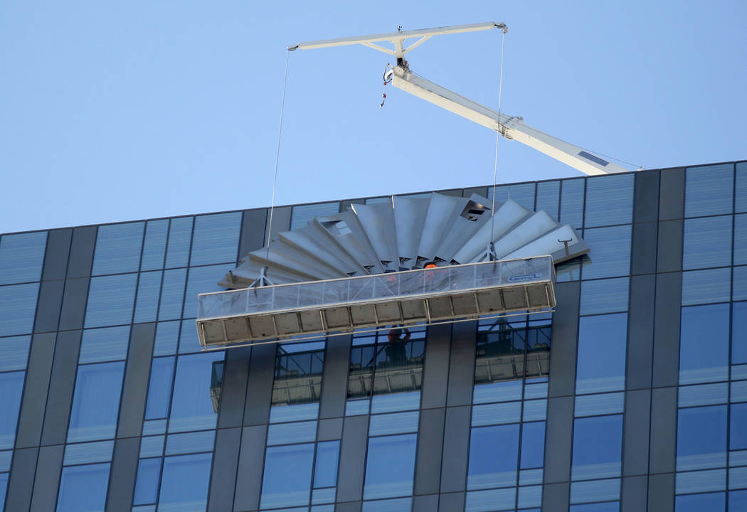 A work crew removes the Mandarin Oriental fan on the top of the Waldorf Astoria on the first day for the new Las Vegas hotel on the Strip Friday, Aug. 31, 2018. Hilton Hotels started to rebrand th ...