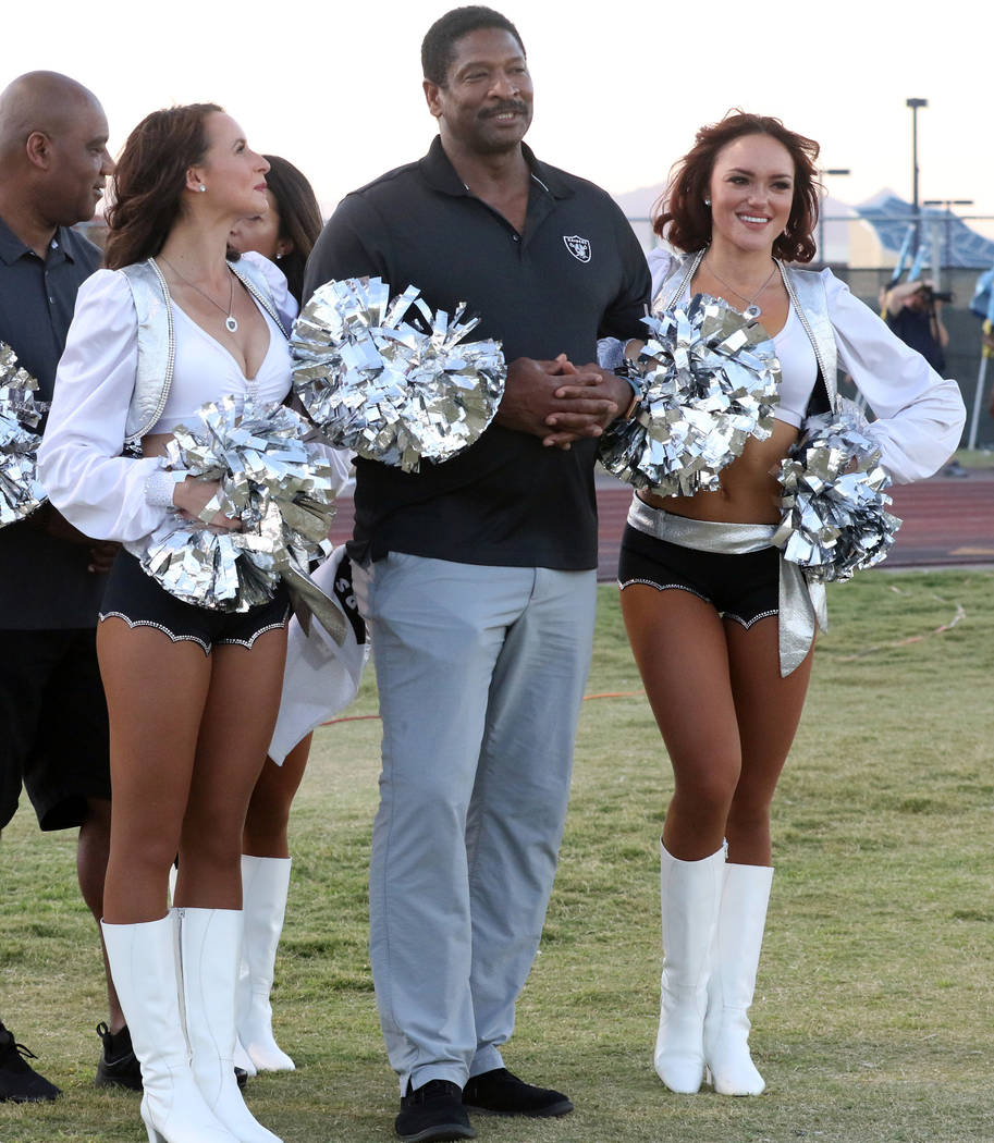 Former Oakland Raiders running back Napoleon McCallum waits with Raiderettes to be called for a coin toss prior to the Foothill Falcons high school football game against Palo Verde in Henderson, F ...