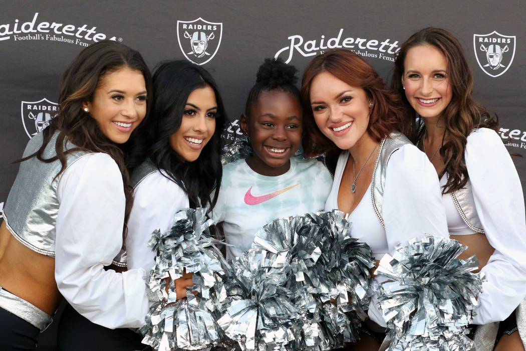 The Raiderettes with 10-year-old Aniyah Thomas, center, at an Oakland Raiders community event during the Foothill Falcons high school football game against Palo Verde high school in Henderson, Fri ...