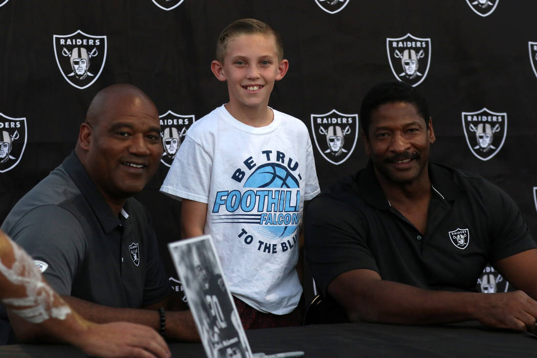 Ridge Tandy of Henderson, center, with former Oakland Raiders Chris McLemore, left, and Napoleon McCallum at a team community event during the Foothill Falcons high school football game against Pa ...