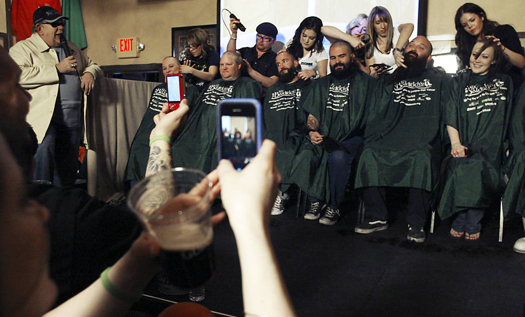 Robin Leach, left, emcees as volunteers get their heads shaved Saturday, March 5, 2011 at McMullan's Irish Pub at a fundraiser to find cures for childhood cancers organized by St. Baldrick's, a vo ...