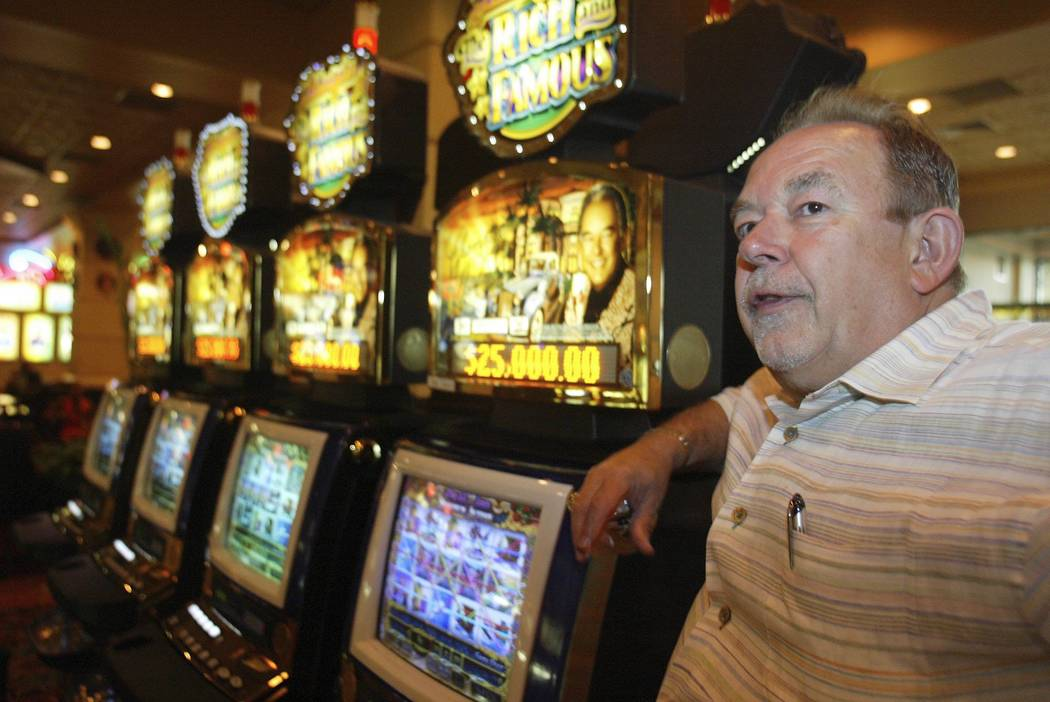 """Living; Robin Leach stands next to a """"Rich and Famous"""" slot machine inside The Orleans in Las Vegas, July, 2004. (Clint Karlsen/Las Vegas Review-Journal)"""