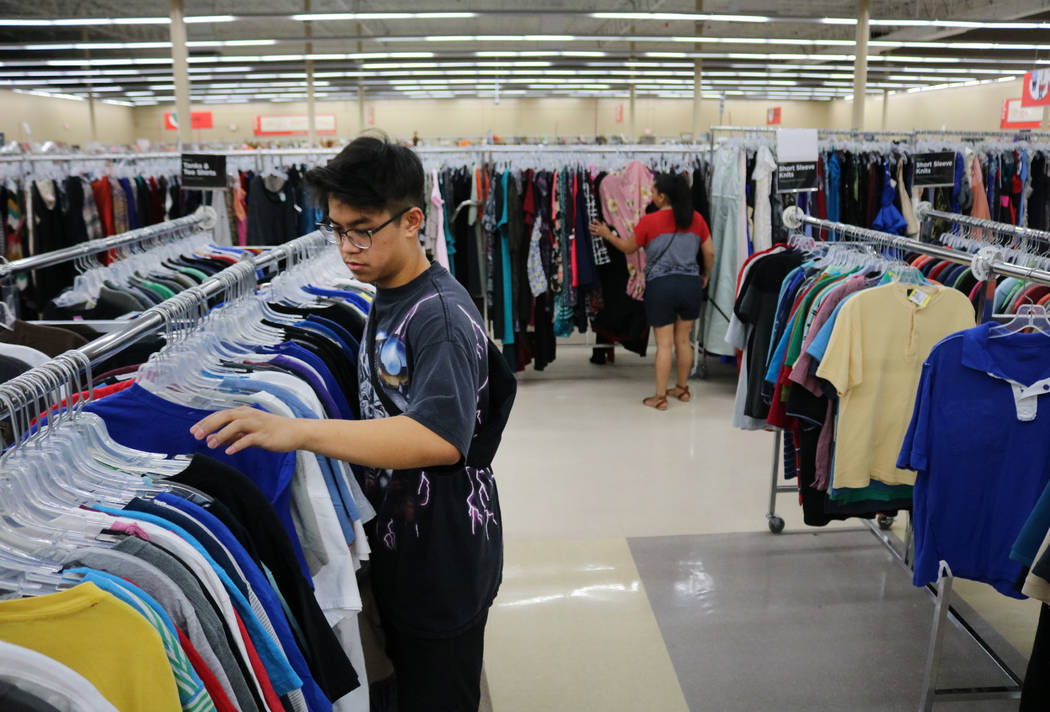 Reanu Elises flips through shirts at Savers thrift shop at the intersection of West Sahara Avenue and South Decatur Boulevard in Las Vegas, Wednesday, Aug. 15, 2018. Elises was there as soon as th ...