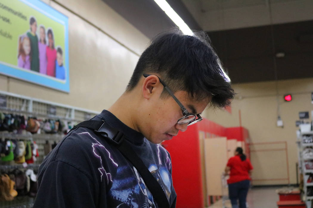 Reanu Elises looks up the value of his prospective purchases on his phone at Savers thrift shop at the intersection of West Sahara Avenue and South Decatur Boulevard in Las Vegas, Wednesday, Aug. ...