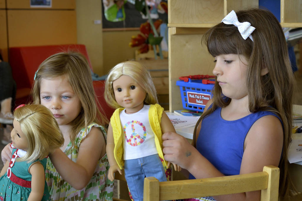 Olivia Alt, 3, left, and her sister Alexa, 7, play with American Girl dolls at the Windmill Library at 7060 W. Windmill Lane in Las Vegas on Thursday, July 26, 2018. The dolls are part of a toy le ...