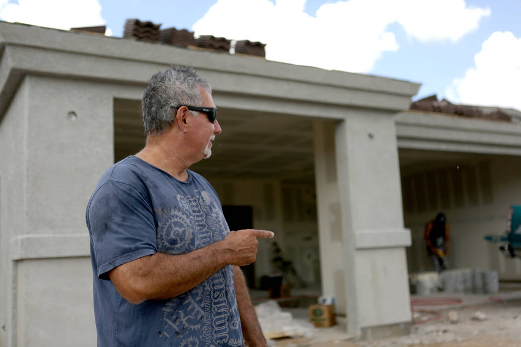 George Long, co-owner of Long's Construction, points to one of the houses he is building on Wildflower Street in a subdivision off Hualapai Mountain Road in Kingman, Ariz. on Friday, August ...