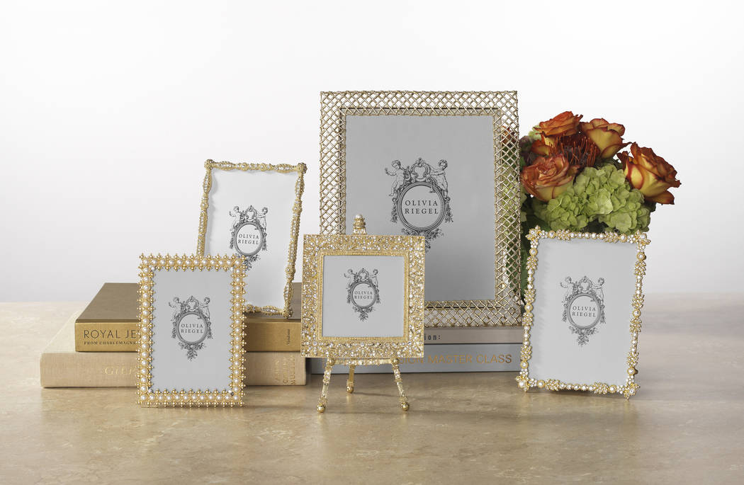 These frames from Olivia Riegel are cast pewter in gold finish with hand-set faux pearls or clear European crystals. An elegant champagne-hued moire silk easel back is designed for vertical or hor ...