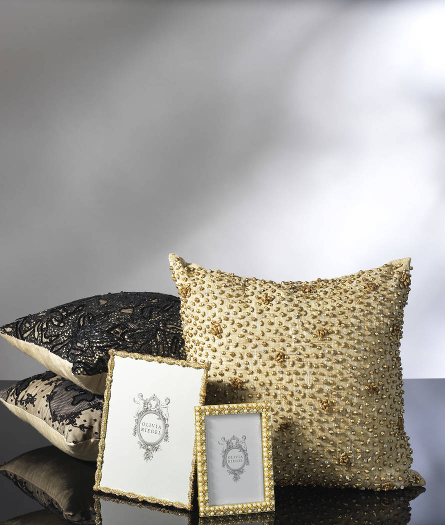 These chic haute couture pillows from Olivia Riegel feature hand-embellishment by master artisans with hundreds of hand-stitched beads, ribbon rosettes and Austrian crystals. (Olivia Riegel)