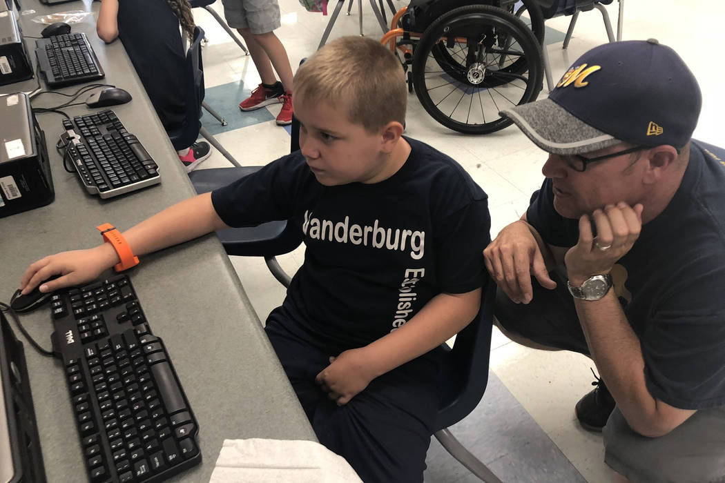 Seven-year-old Dylan Chalmers, a second-grade student with cerebral palsy, works on a computer after school at Vanderburg Elementary School with his dad, Scott, on Aug. 24. Dylan was rec ...