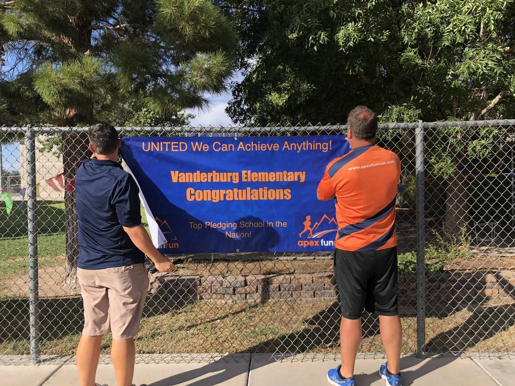 Frank Endellicate and Rob Wiatt, employees with Apex Fun Run, hang a banner at Vanderburg Elementary School in Henderson on Aug. 24, celebrating the school's achievement. Seven-year-old Dylan Chal ...