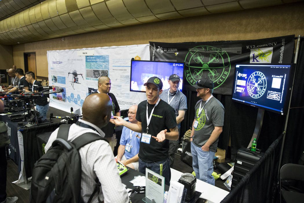 Exhibitor Chris Cernuto, center, founder of the Las Vegas Drone Club, speaks with Shawn Gibson, during the InterDrone conference at the Rio Convention Center in Las Vegas, Wednesday, Sept. 6, 2017 ...