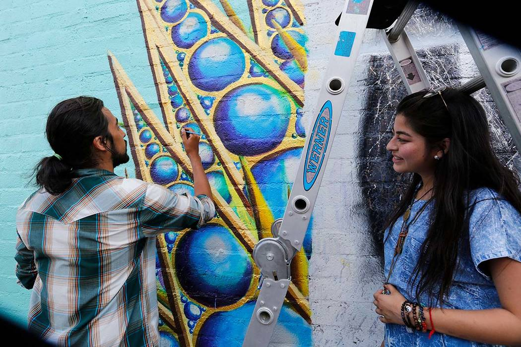 Las Vegas artist Ricardo Limones paints a mural as his friend artist Katherine Cardona looks on during First Friday Las Vegas, a monthly art festival, located in downtown Las Vegas Arts District, ...