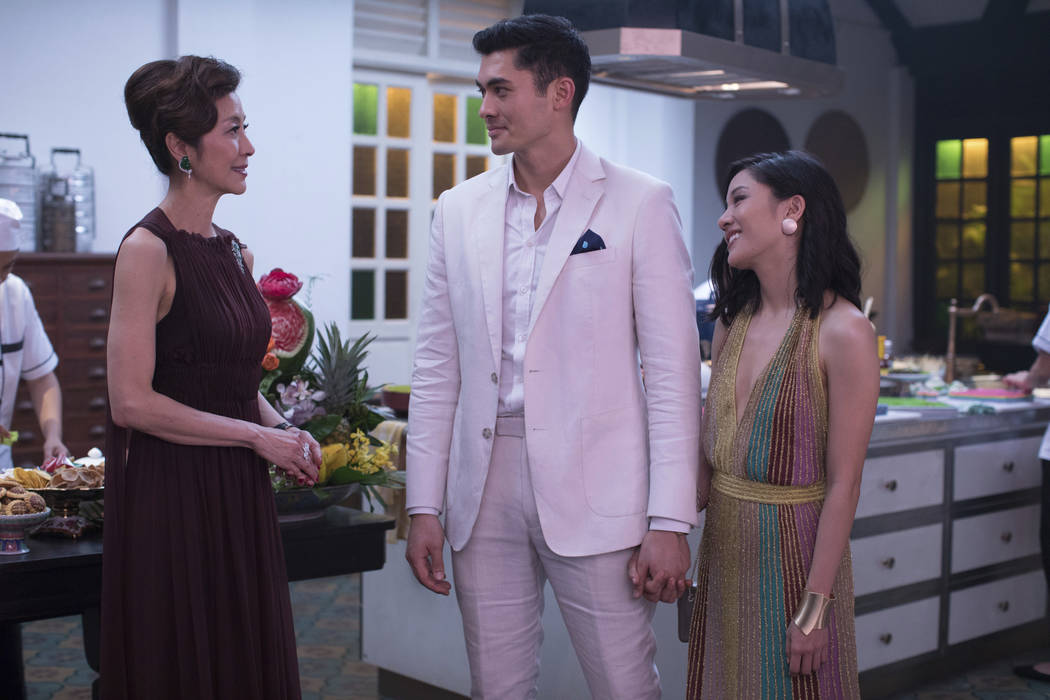 "Michelle Yeoh, from left, Henry Golding and Constance Wu stars in a scene from the film ""Crazy Rich Asians."" (Sanja Bucko/Warner Bros. Entertainment via AP)"