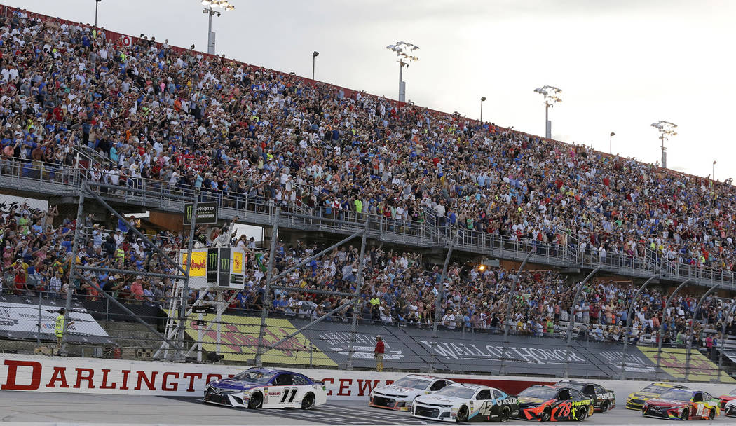 Denny Hamlin (11) leads the pack to start the NASCAR Cup Series auto race at Darlington Raceway, Sunday, Sept. 2, 2018, in Darlington, S.C. (AP Photo/Terry Renna)