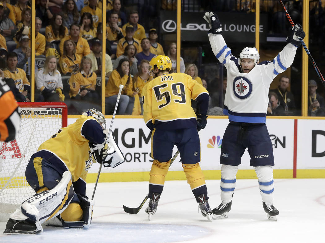 Winnipeg Jets center Paul Stastny, right, celebrates after teammate Tyler Myers, not shown, scored a goal against Nashville Predators goalie Pekka Rinne, left, of Finland, during the first period ...