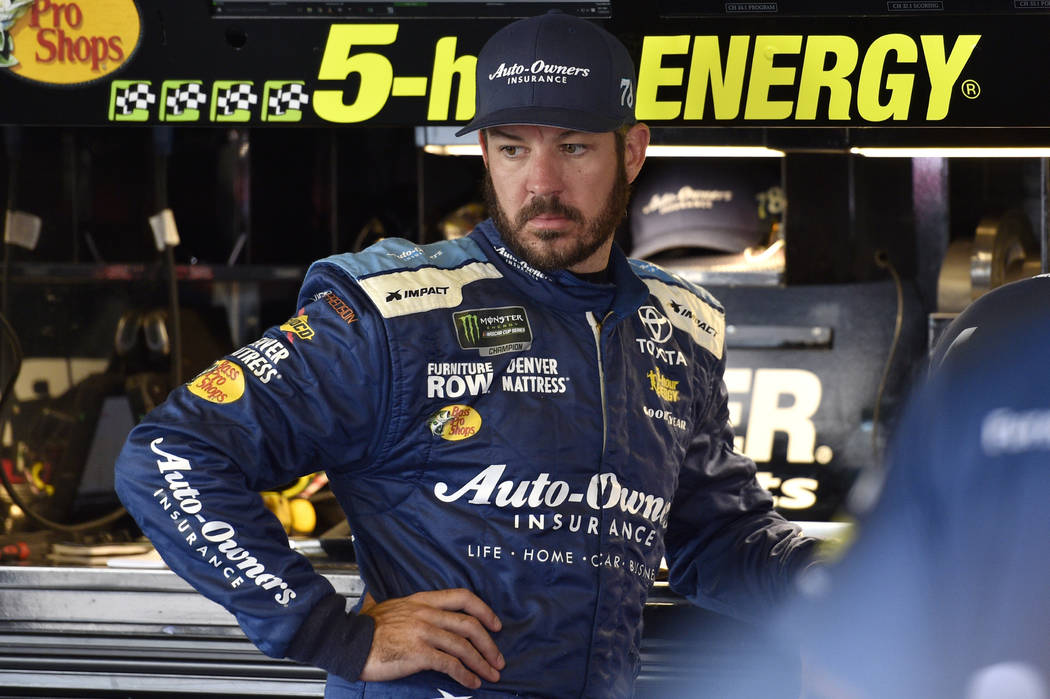 Martin Truex Jr. looks over his car in the garage during practice for Sunday's NASCAR Cup Series auto race, Saturday, July 28, 2018, in Long Pond, Pa. (AP Photo/Derik Hamilton)