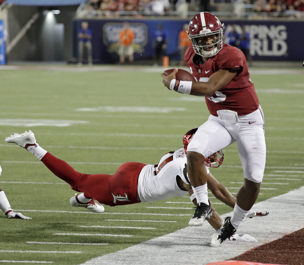 Alabama quarterback Tua Tagovailoa, right, is forced out of bounds by Louisville safety Dee Smith after a short gain during the first half of an NCAA college football game Saturday, Sept. 1, 2018, ...