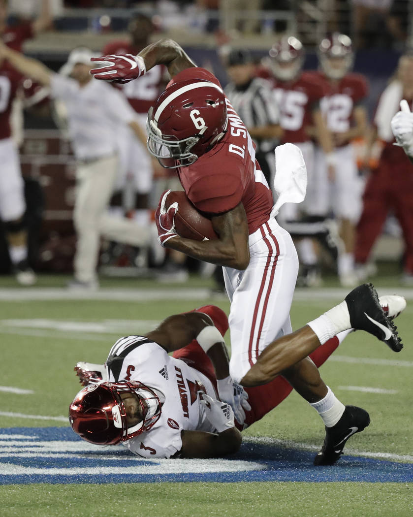 Alabama wide receiver DeVonta Smith (6) is stopped by Louisville cornerback Cornelius Sturghill after a reception during the first half of an NCAA college football game Saturday, Sept. 1, 2018, in ...