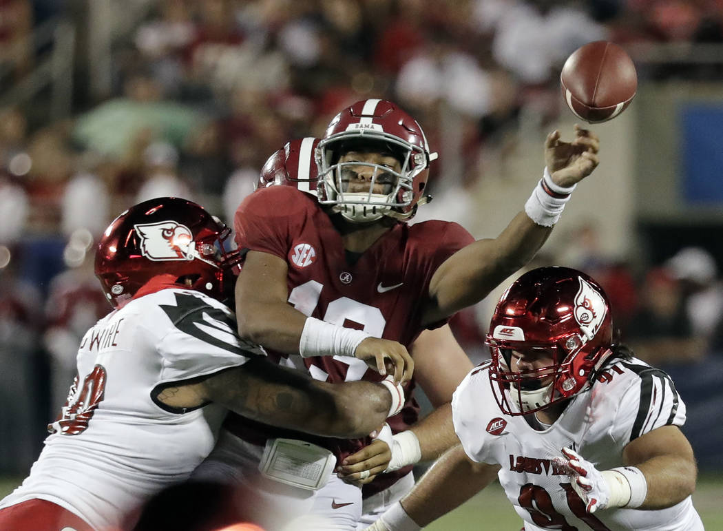 Alabama quarterback Tua Tagovailoa, center, manages to get off a pass as he is hit by Louisville defensive lineman Jared Goldwire, left, and defensive end Derek Dorsey (91) during the first half o ...
