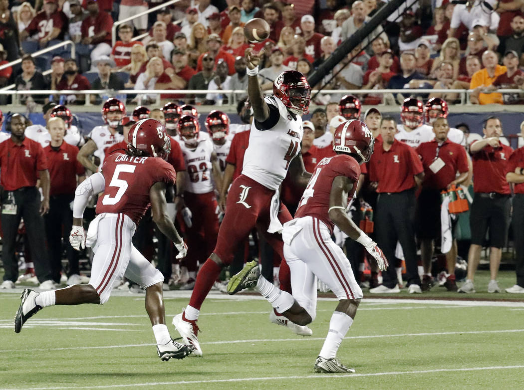 Louisville quarterback Jawon Pass, center, throws an 11-yard pass for a touchdown as Alabama defensive backs Shyheim Carter (5) and Deionte Thompson, right, chase him during the second half of an ...