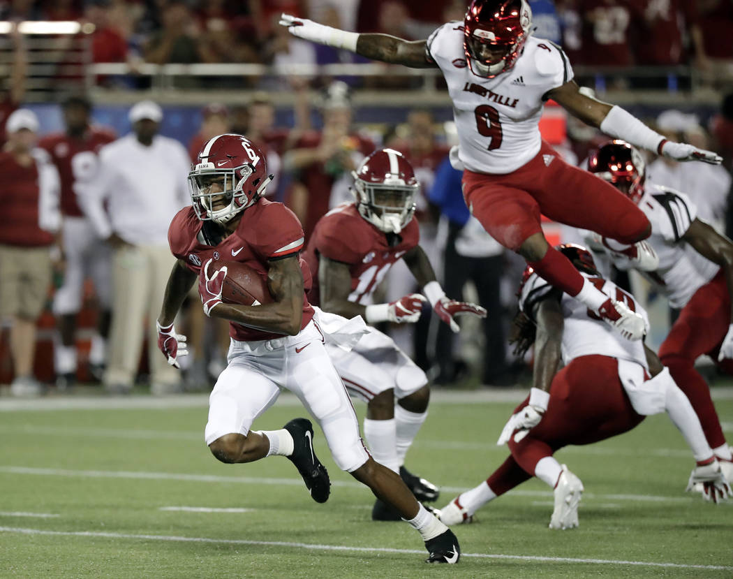 Alabama wide receiver DeVonta Smith, left, runs past Louisville linebacker C.J. Avery (9) after a reception during the first half of an NCAA college football game, Saturday, Sept. 1, 2018, in Orla ...
