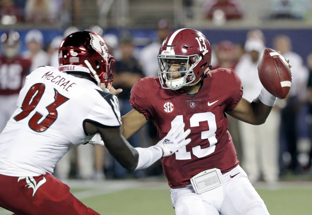 Alabama quarterback Tua Tagovailoa (13) looks for a receiver as he is pressured by Louisville defensive end Gary McCrae (93) during the first half of an NCAA college football game, Saturday, Sept. ...