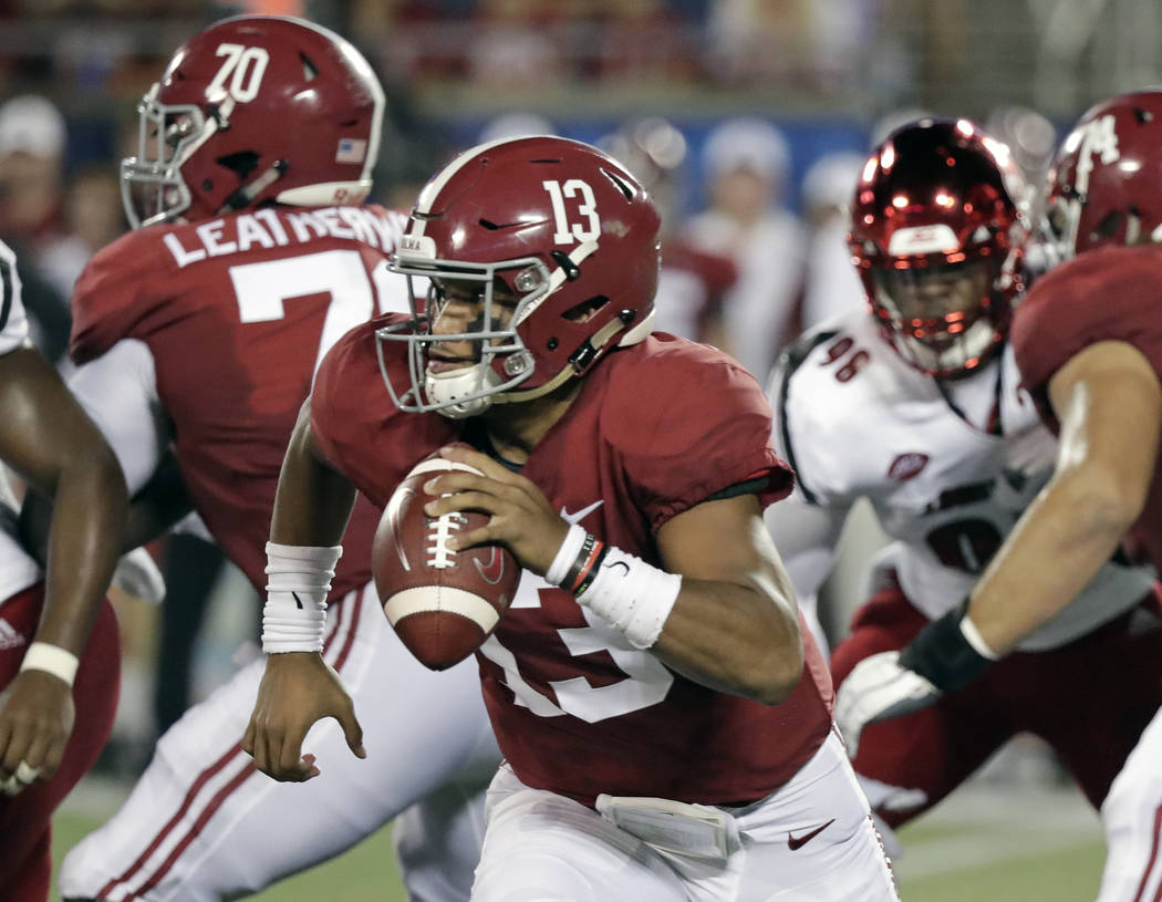 Alabama quarterback Tua Tagovailoa (13) scrambles while looking for a receiver against Louisville during the first half of an NCAA college football game, Saturday, Sept. 1, 2018, in Orlando, Fla. ...