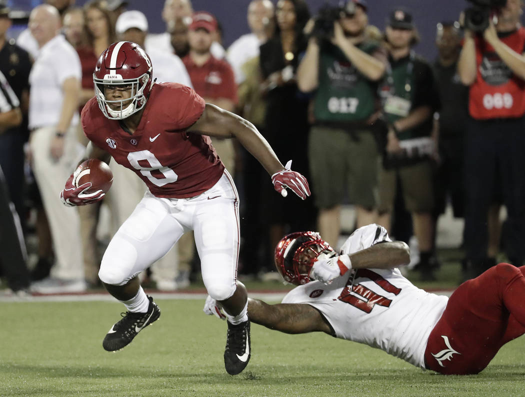 FILE - In this Sept. 1, 2018, file photo, Alabama running back Josh Jacobs (8) slips past Louisville defensive lineman Michael Boykin (41) for a gain during the first half of an NCAA college footb ...