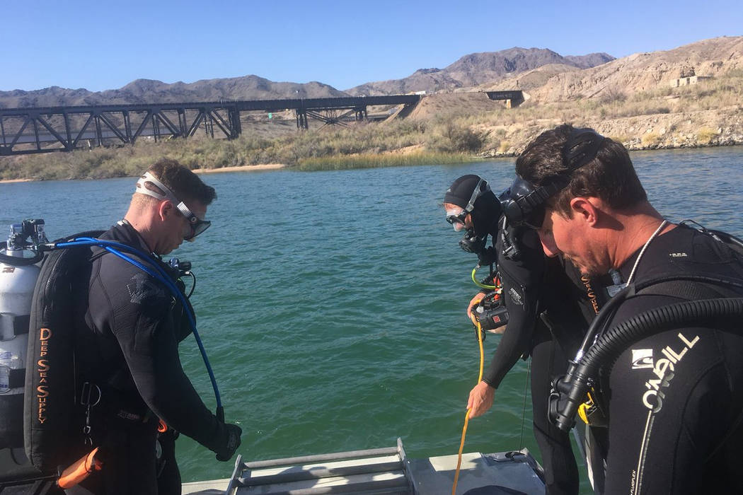 In this photo released by Los Angeles Sheriff Department Special Enforcement Bureau their dive team assists San Bernardino County Sheriffs in the search for three missing persons in the Colorado r ...