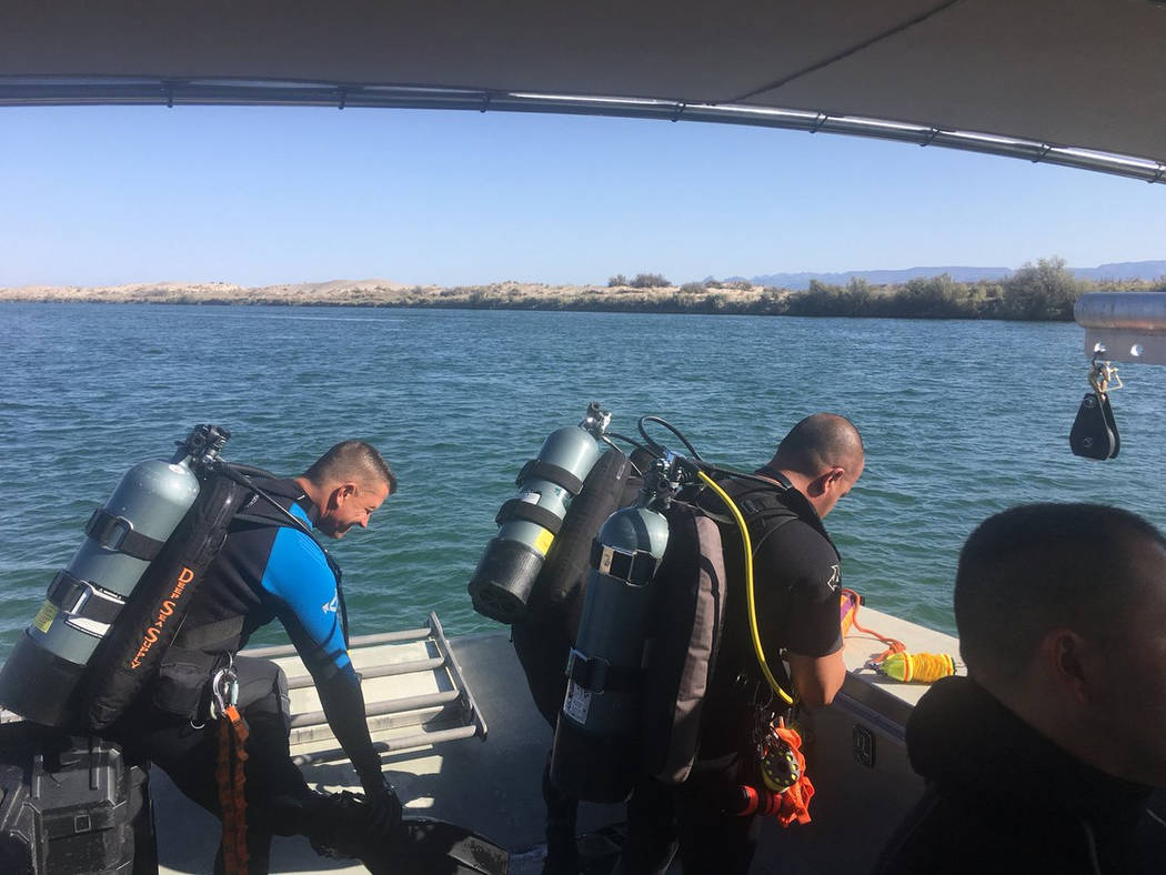 This photo released by Los Angeles Sheriff Department Special Enforcement Bureau shows their dive team assisting San Bernardino County Sheriffs in search of three missing persons in the Colorado r ...