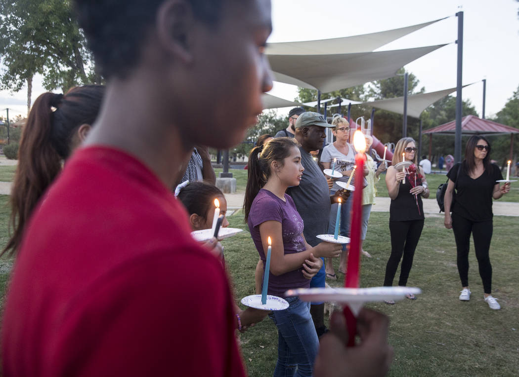 Ares Mendiola, middle, 11, holds a candle during a vigil for Levi Echenique, Daniel Theriot and Dejah Hunt at Sunset Park on Tuesday, Sept. 4, 2018, in Las Vegas. Benjamin Hager Las Vegas Review-J ...