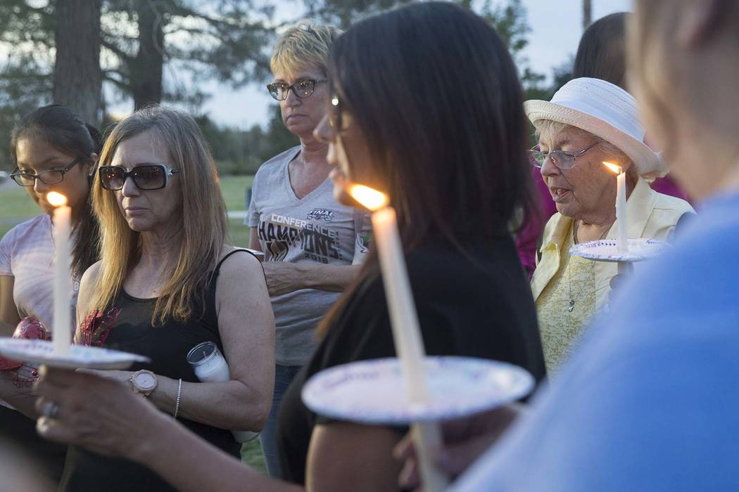 Carrol Carter, right, leads a prayer during a vigil for Levi Echenique, Daniel Theriot and Dejah Hunt at Sunset Park on Tuesday, Sept. 4, 2018, in Las Vegas. (Benjamin Hager/Las Vegas Review-Journ ...
