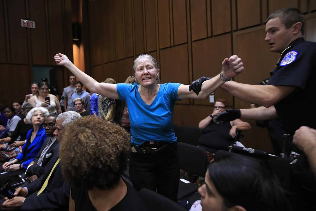 A protester is restrained by a U.S. Capitol Police officer during a Senate Judiciary Committee nominations hearing on Supreme Court nominee Brett Kavanaugh, on Capitol Hill in Washington, Tuesday, ...