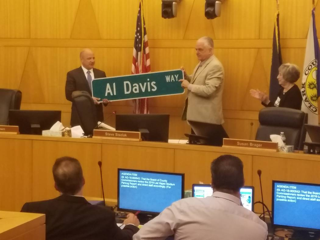 "Oakland Raiders President Marc Badain accepts a street sign for ""Al Davis Way"" from Clark County Commissioner Steve Sisolak at a Clark County Commission meeting Wednesday, Sept. 5, 2018. (Richard ..."