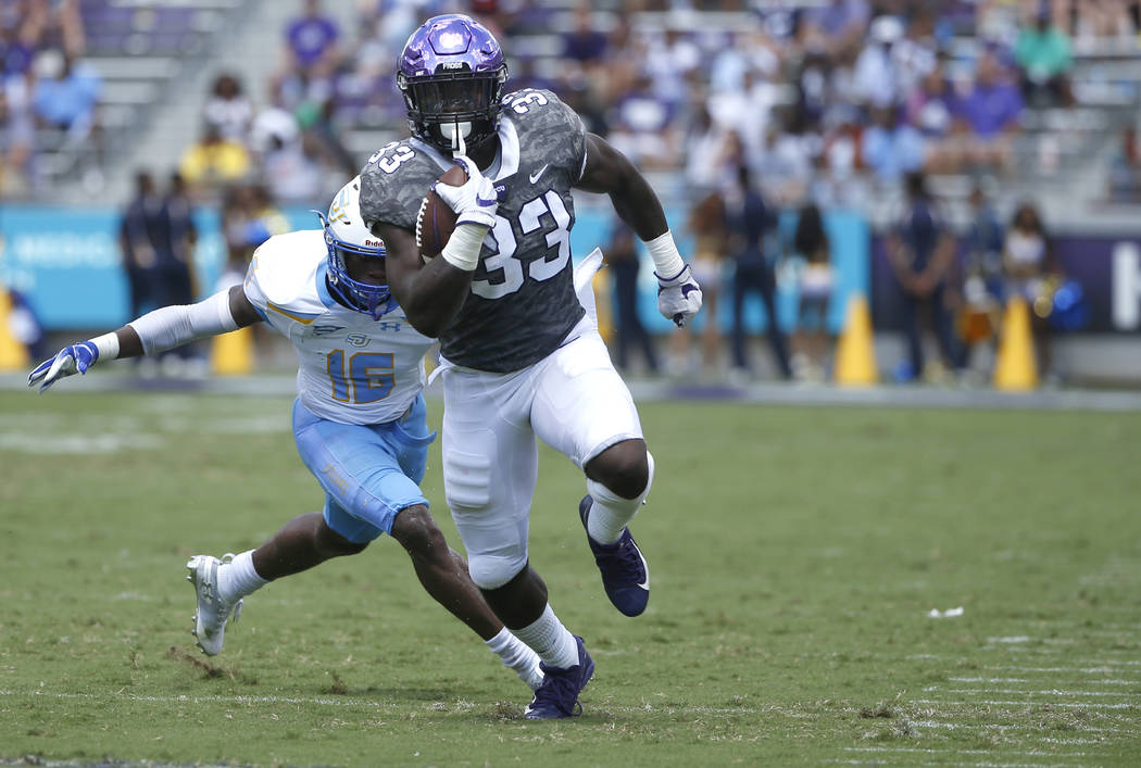 TCU running back Sewo Olonilua (33) runs for a first down as Southern University defensive back Kaycee Ntukogo (16) closes on during the first half of an NCAA college football game Saturday, Sept. ...
