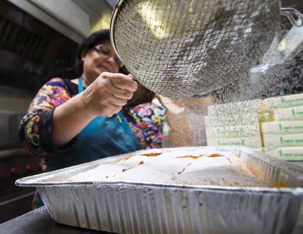 Volunteer Kiki Mavrantonis adds powdered sugar to bougatsa, a cream-filled phyllo pastry, at St. John the Baptist Greek Orthodox Church ahead of the annual Las Vegas Greek Food Festival, slated to ...