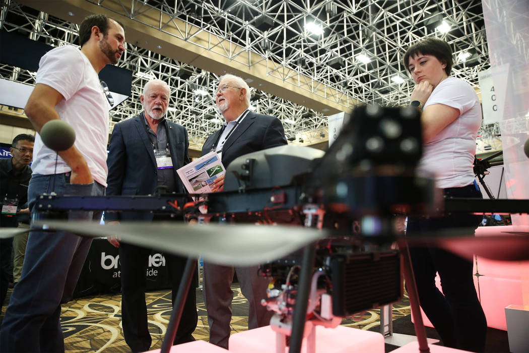 Blaine Horne, from left, director of engineering solutions for PrecisionHawk, shows a drone to Tim Archer and Jimmy Tubbs of Blue Sky Innovations, during the InterDrone convention at the Rio hotel ...