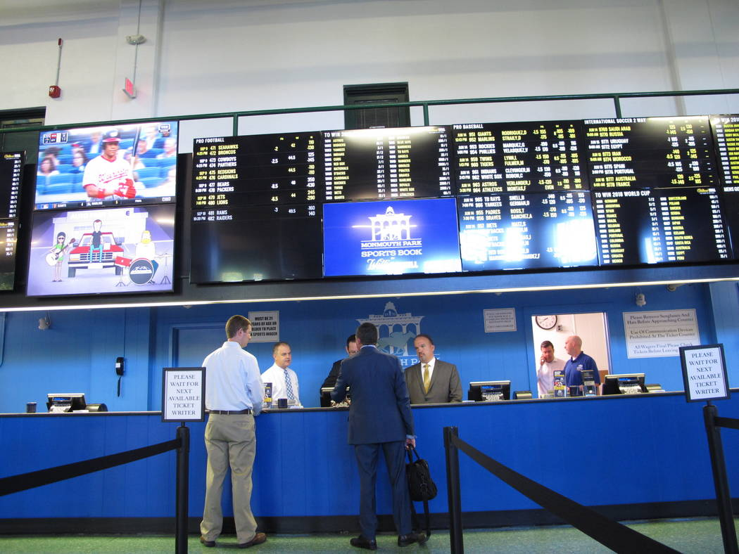 This June 14, 2018 photo shows staff at Monmouth Park racetrack in Oceanport N.J. preparing to begin taking sports bets moments before it became legal in New Jersey. (AP Photo/Wayne Parry)