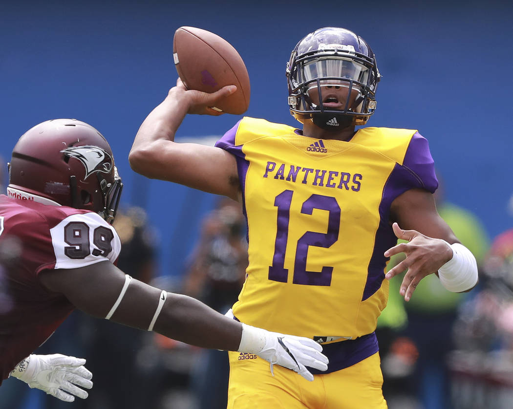 Prairie View A&M quarterback Jalen Morton (12) passes under pressure from North Carolina Central defender Chuck Manning during the first half of the MEAC-SWAC Challenge college football game o ...
