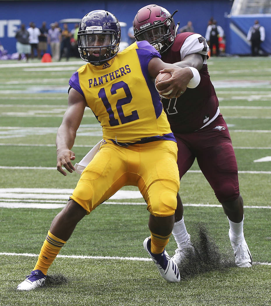 Prairie View A&M quarterback Jalen Morton (12) puts a move on North Carolina Central defender Kawuan Cox on his way to the end zone on a quarterback keeper during the first quarter of the MEAC ...