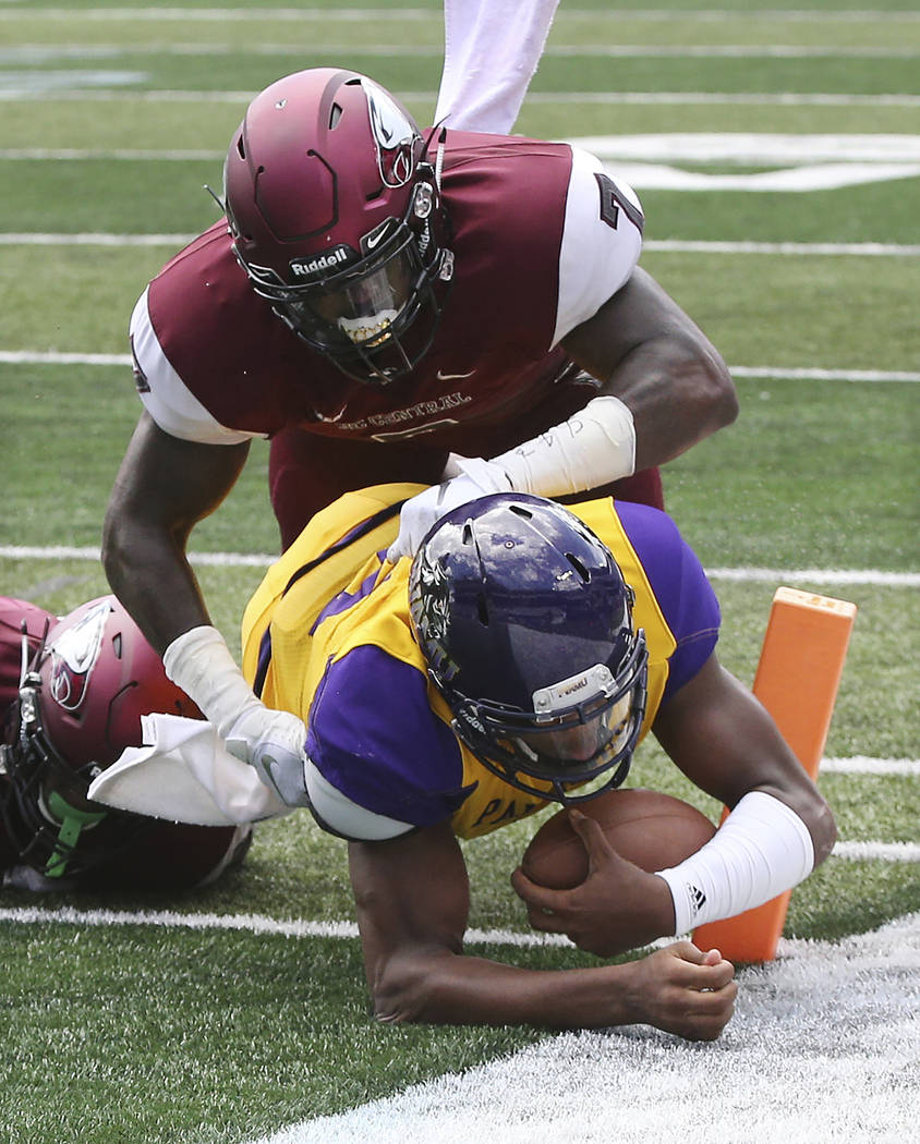 Prairie View A&M quarterback Jalen Morton, bottom, gets into the end zone past North Carolina Central defender Kawuan Cox, top, on a quarterback keeper during the first quarter of the MEAC-SWA ...