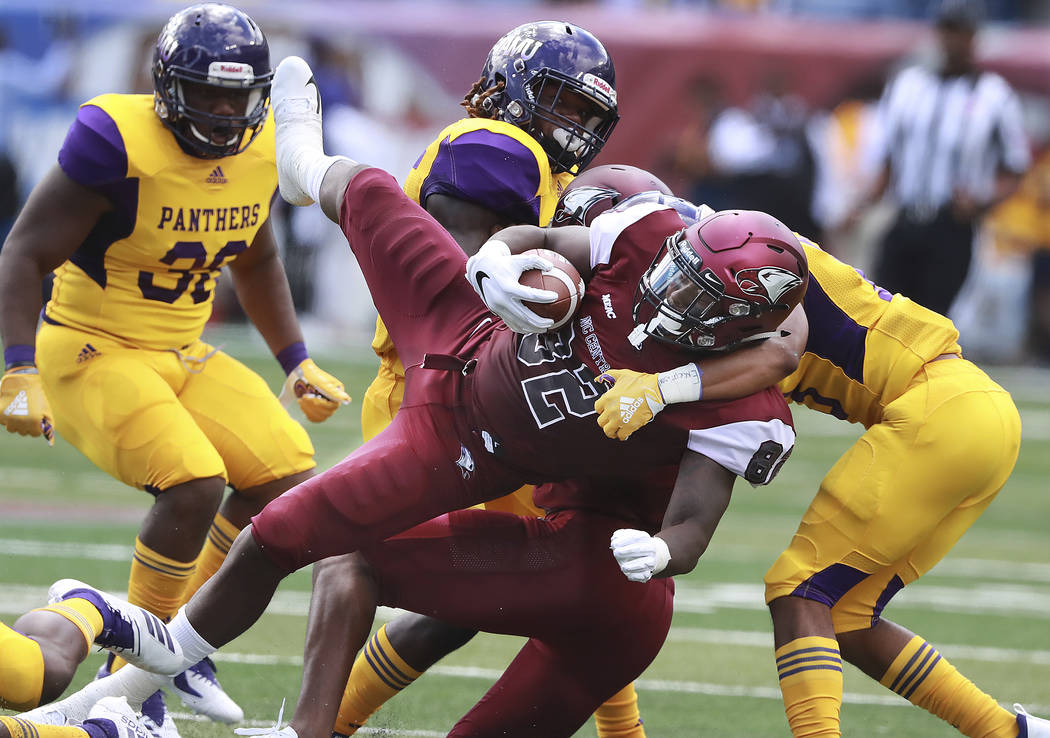 North Carolina Central tight end Josh McCoy, center, is upended by Prairie View A&M defenders during the first quarter of the MEAC-SWAC Challenge college football game on Sunday, Sept 2, 2018, ...
