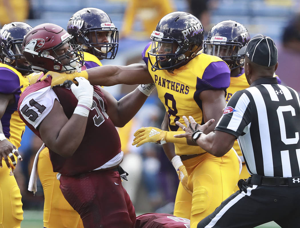 North Carolina Central offensive lineman Nick Leverett (51) and Prairie View A&M wide receiver Quinton Bell get into a shoving match during the first half of the MEAC-SWAC Challenge college f ...
