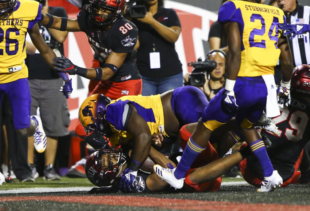 UNLV Rebels quarterback Armani Rogers (1) scores a touchdown under Prairie View A&M Panthers defensive tackle Jason Dumas (92) during the first half of a football game at Sam Boyd Stadium in L ...